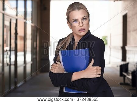 Businesswoman In Eyeglasses In A Business Suit Holds Tightly A Folder With Important Documents And I