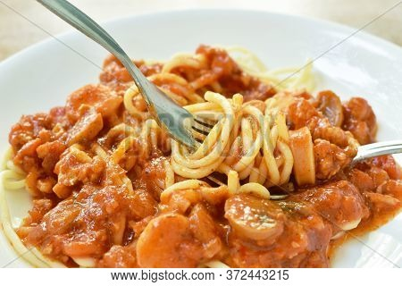 Fried Spaghetti Topping Slice Sausage With Chop Pork And Ketchup Roll Over Fork On Plate