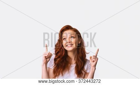 Look Up. Millennial Girl Pointing Fingers Upward Posing In Studio Over White Background. Panorama