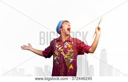 Young Emotional Artist With Open Mouth Gesturing With Paintbrush. Happy Painter In Shirt And Bandana