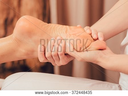 Foot Reflexology, Foot Massage Close-up. Masseur Pushing On Special Points On The Foot, Massage Trea