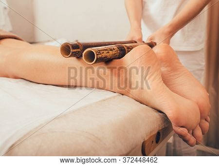 Leg Massage With Bamboo Sticks. Massage Therapist Doing Thai Massage With Bamboo Sticks