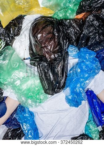Young Man With Plastic Bag On Face, Lying Down, Surrounded By Plastic Bags. Horizontal View.