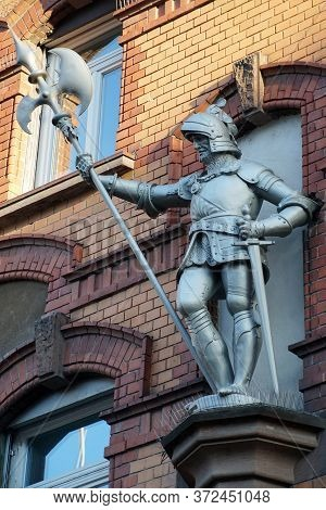 Knight Statue On A Residential Building. The Knight In His Shiny Silver Armor Stands High On A Pedes