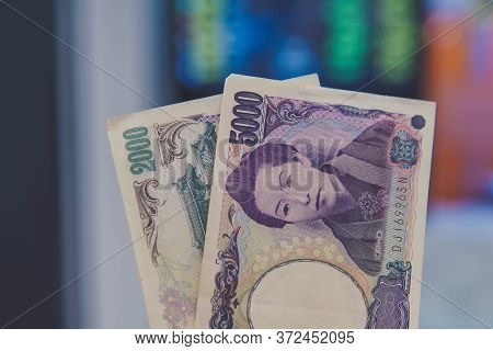 Japanese Yen Banknote And The Currencies Exchange Rate Table As The Baackground.  The Yen Is The Off