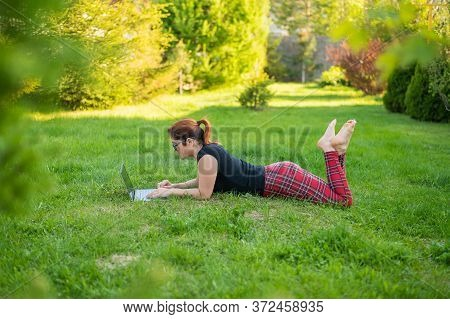 Woman Is Shopping On A Laptop While Lying On Her Stomach On Green Grass In A Park. A Student With Tw