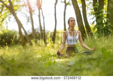 Young woman meditating in Lotus position in nature