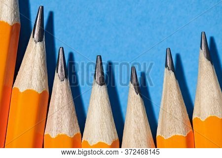 graphite pencils on a blue background macro photo, school and office supplies