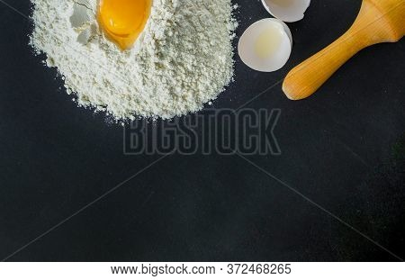 Close-up Of White Wheat Flour With A Broken Egg And Rolling Rolling Of Dough. Black Background. Hori
