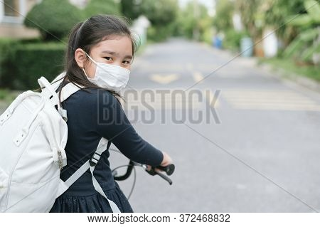Back To School. Asian Child Girl Wearing Face Mask With Backpack Biking A Bicycle And Going To Schoo