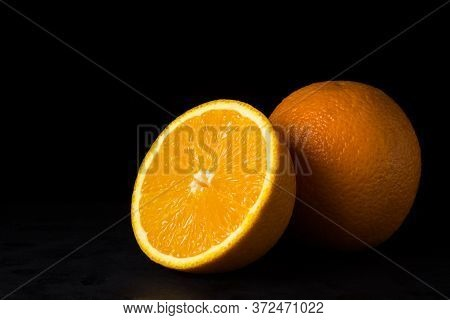 Oranges On A Black Background. One Orange Is Cut In Half, The Other Is Whole. Tropical Fruits.