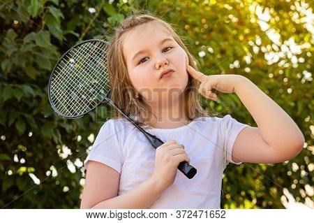 A Little Girl Jokingly Makes A Glamorous Face. Cute Little Girl Playing Badminton Outdoors On Warm A