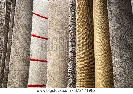 Samples Of Synthetic Carpets Of Various Patterns Of White Yellow Gray Color Suspended On The Crossba