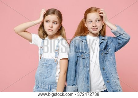 Pensive Puzzled Little Kids Girls 12-13 Years Old In White T-shirt, Denim Clothes Isolated On Pink B