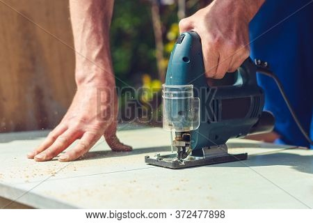 A Carpenter Saws A Wooden Cloth With An Electric Jig Saw.