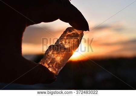 A Silhouette Image Of A Clear Quartz Crystal Being Held Against A Orange Sunset.
