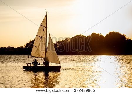 Yacht With Two White Sails And People On The Lake. Sunset On The Water. Summer Calm Rest On Lake, Ya