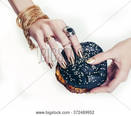 Hands Of Rich Woman With Golden Manicure And Jewelry Holding Black Hamburger Closeup Fashion Concept
