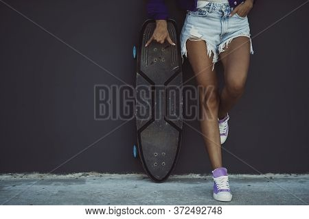 Tanned Girl With A Skateboard Is Standing In Front Of Grey Wall.