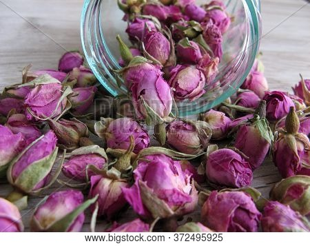 Close Up Of Pink Dried Rose Buds (herbal Tea) In Glass Bottle On Wooden Background. Reduced Symptoms