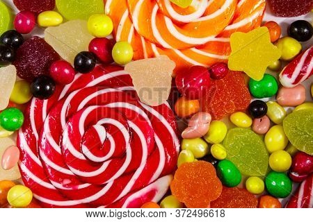Background Of Colorful Chocolate Candies, Lollipops, Candy Cane And Jelly Sweets