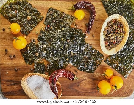 Crispy Nori Seaweed With Cherry Tomatoes And On A Wooden Board. Japanese Food Nori. Dried Sheets Of