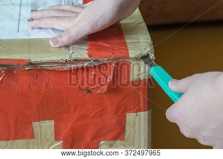 Man Unpacking Cardboard Box With Cutter. An Old Battered Cardboard Box. Box Wrapped With Tape.