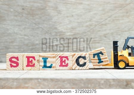 Toy Forklift Hold Letter Block T To Complete Word Select On Wood Background