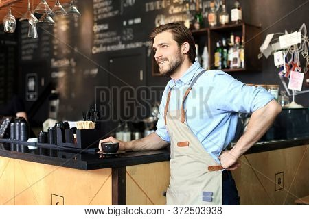 Shot Of Happy Young Bar Owner Standing Near The Counter And Looking Away Smiling.
