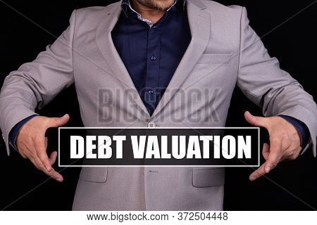 Debt Valuation Text Is Written On The Background Of A Businessman In A Gray Suit. Business Concept