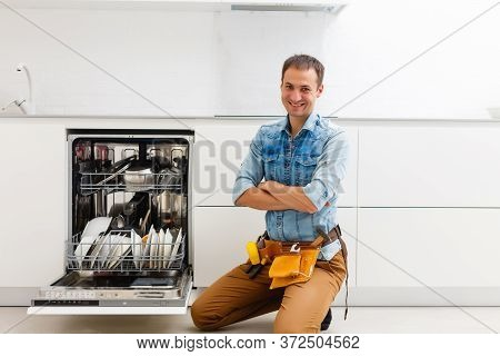 Plumber. Smiling Handsome Plumber Standing With Crossed Arms And Looking At Camera In Kitchen