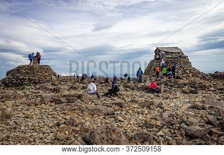 Ben Nevis / Uk - August 24 2019: Hikers On The Ben Nevis Summit, In The Scottish Highlands.