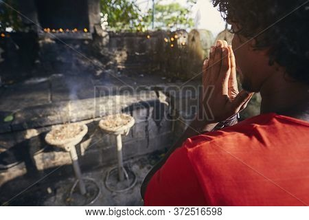 Hands Of A Praying Man.(buddhist) Praying Against Shrine With Incenses. Dambulla, Sri Lanka.