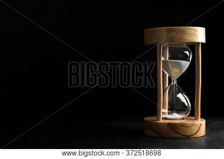 Sandglass On Table Against Black Background, Space For Text. Pareto Principle Concept