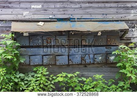 Old Mailboxes On A Wooden Wall Of A Residential Building Close Up