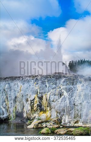 Active Geyser Erupting High Above Sulphur Covered Rocks