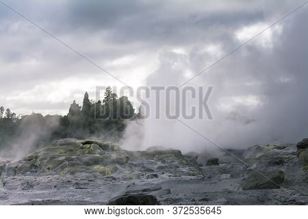 Geothermal Area With Active Geysers Erupting Above Rocks