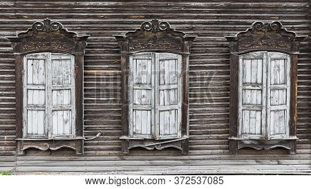 Shuttered Windows Of An Old Wooden Residential Building Close Up