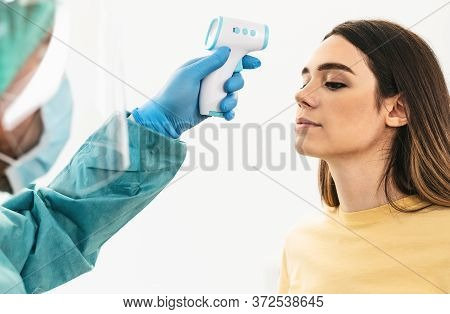 Doctor Measuring Temperature With New Digital Thermometer To Young Woman Patient During Corona Virus
