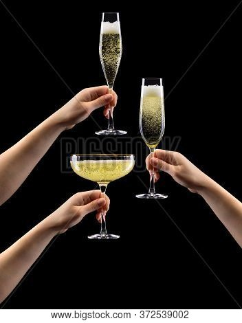 Set Of Hands Holding Glass Of Sparkling Champagne Isolated On Black.