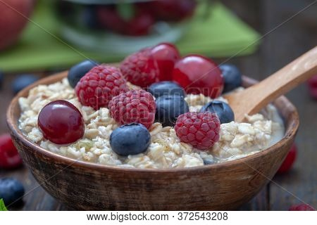Rolled Oats With Blueberries And Raspberries, Closeup Healthy Breakfast Cereal Oat Flakes In Bowl On