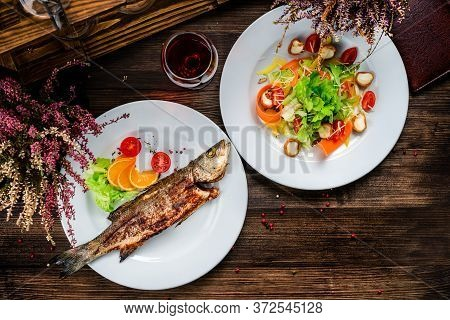Grilled Sea Bass On The Wooden Board, Seabass With Salad, Two Dishes On The Table Top View, Flat Lay