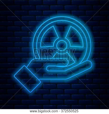 Glowing Neon Line Radioactive In Hand Icon Isolated On Brick Wall Background. Radioactive Toxic Symb