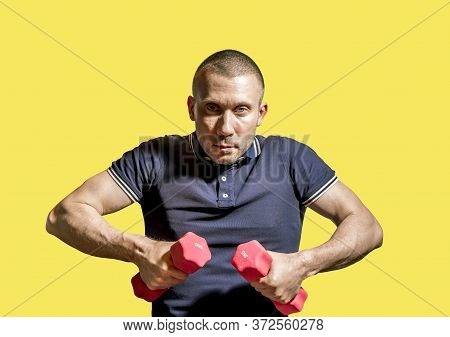 A Stern Man Holds Dumbbells In His Hands On A Yellow Background .