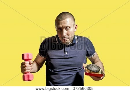A Man Holds A Black Burger In One Hand And A Dumbbell In The Other On A Yellow Background. A Man Cho