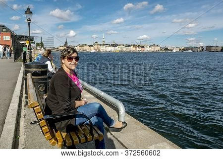 Stockholm, Sweden. 04 September 2015. A Woman Sits On A Bench On The Embankment In Stockholm.