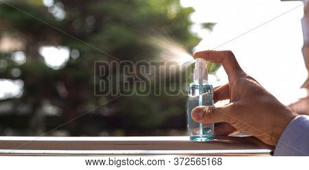 Young Man Uses A Spray Of Alcohol To Get Rid Of Bacteria And Viruses, Inhibition And Prevention Of C