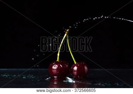 Cherry On A Black Background. Two Cherries Stand On The Water. A Stream Of Water Over A Cherry.