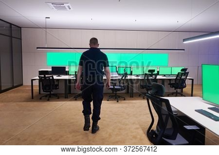 young male security operator walking through data system control room Working at workstation with multiple displays, security guard working on multiple monitors  Male computer operator monitoring from
