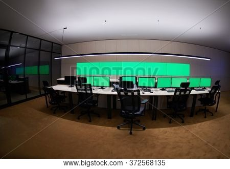 Empty interior of big modern security system control room with blank green screens, workstation with multiple displays, monitoring room with at security data center  Empty office, desk, and chairs at